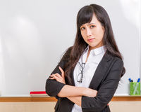 Asian teacher frowning in front of whiteboard Stock Photo