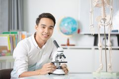 Asian teacher with microscope and skeleton model.  Royalty Free Stock Image