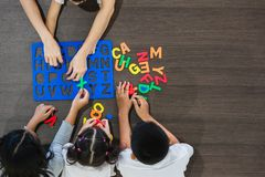 Asian teacher play Alphabet puzzle with students