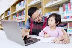 Asian teacher teaches female student in library. Asian male teacher teaches female student with laptop computer in a library Stock Photos