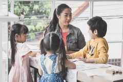 Asian Teacher teaching children in kindergarten art classroom royalty free stock photos
