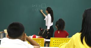 Asian teacher writes math problem on green board. Asian teacher writes math problem on green board, student pay attention to her consciously, in math class stock video