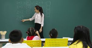 Asian teacher writes math problem on green board. Asian teacher writing math problem on green board, student pay attention to her consciously, in math class stock video