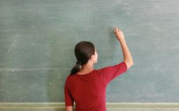 Asian teacher writing on blackboard with chalk in classroom. Educations concept stock image