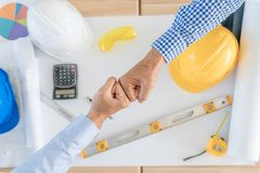 Asian team Business or engineer and architects partners giving f. Ist bump after complete deal. Successful teamwork partnership in an office. businessman with royalty free stock images