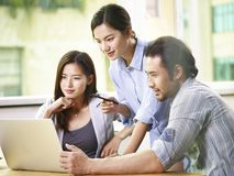 Asian team of business people working together in office royalty free stock photography