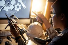 Asian technical engineer repairing drone. Asian technical engineer changing spare propeller repairing drone with fixing tools on the desk. Male technician Royalty Free Stock Images