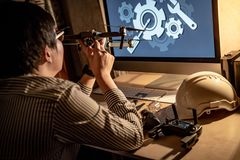 Asian technical engineer checking drone gimbal camera. Repairing drone with computer and tools on desk. Male technician fixing or maintenance drone. Unmanned Stock Image