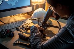 Asian technical engineer using screwdriver for repairing drone. Asian technical engineer using electric screwdriver for repairing drone with computer and tools Royalty Free Stock Photos