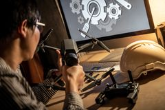 Asian technical engineer using screwdriver for repairing drone. Asian technical engineer using electric screwdriver for repairing drone with computer and tools Stock Image