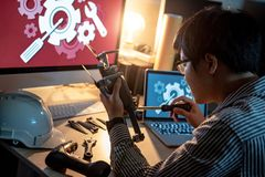 Asian technical engineer using screwdriver for repairing drone. With computer and other tools on desk. Male technician fixing or maintenance drone. Unmanned Royalty Free Stock Image