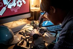 Asian technical engineer using screwdriver for repairing drone. With computer and other tools on desk. Male technician fixing or maintenance drone. Unmanned Stock Photography