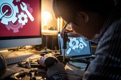 Asian technical engineer using screwdriver for repairing drone. With computer and tools on desk. Male technician fixing or maintenance drone. Unmanned aerial Royalty Free Stock Image