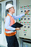 Asian technician at panel on construction site. Asian Indonesian Technician or electrician making function test on Panel or switchbox for the control of air Stock Photography