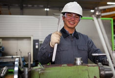 Asian technician at tool workshop. Technician working in factory looking at camera Royalty Free Stock Photo