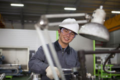 Asian technician at tool workshop. Modern industrial machine operator working in factory Royalty Free Stock Images
