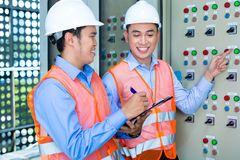 Asian technicians at panel on construction site. Asian Indonesian Technician or electrician making function test on Panel or switchbox for the control of air Stock Images