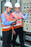 Asian technicians at panel on construction site. Asian Indonesian Technician or electrician making function test on Panel or switchbox for the control of air Stock Photo