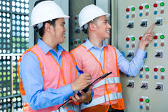 Asian technicians at panel on construction site. Asian Indonesian Technician or electrician making function test on Panel or switchbox for the control of air Royalty Free Stock Images