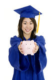 Asian teenager wearing blue graduation gown and holding piggy bank Royalty Free Stock Photography