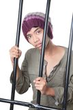 Asian teen behind prison bars. Asian male teenager with cap and grunge shirt holding and standing behind prison bars, looking wondering and innocently at cam royalty free stock photos