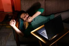 Asian teen bored and watching video on a laptop Royalty Free Stock Photography