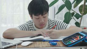Asian teen boy doing your homework with laptop computer at home. stock video