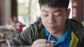 Asian teen boy drinking water from a plastic tube sitting at home stock video footage