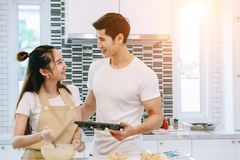 Asian teen couple are helping to make dinner. And bakery together happily. On Valentine`s Day in their home Royalty Free Stock Photography