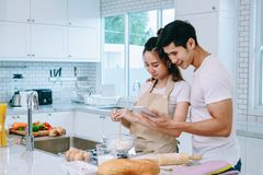 Asian teen couple are helping to make dinner. And bakery together happily. On Valentine Day in their home Royalty Free Stock Photo