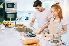 Asian teen couple are helping to make dinner. And bakery together happily. On Valentine`s Day in their home Royalty Free Stock Photos