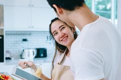 Asian teen couple are helping to make dinner. And bakery together happily. On Valentine`s Day in their home Royalty Free Stock Image