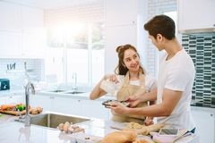 Asian teen couple are helping to make dinner. And bakery together happily. On Valentine`s Day in their home Royalty Free Stock Photo