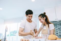 Asian teen couple are helping to make dinner. And bakery together happily. On Valentine`s Day in their home Royalty Free Stock Images
