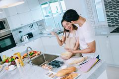 Asian teen couple are helping to make dinner. And bakery together happily. On Valentine`s Day in their home Stock Photos