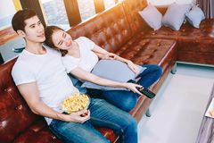 Asian teen couple are helping to make dinner. Asian teen couple watching TV together happily. Eating popcorn after he had eaten dinner already in their beautiful Stock Photo