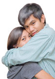 Asian teen couple love. Asian and Indian mixed teenager couple in a tight, loving and tender hug. Girl hiding in boy's arms. Isolated over white Stock Photos