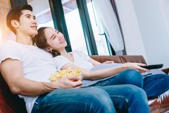 Asian teen couple watching TV together happily. Royalty Free Stock Photography