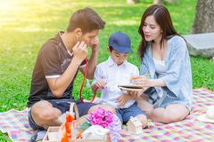 Asian teen family teaching son homework while picnic stock images