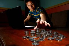 Asian Teen in front of laptop computer and reaching for a stack of coins Stock Photo