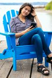 Asian teen girl on blue chair by lake using smartphone stock photo