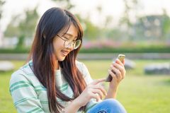 Asian teen girls play smartphone in the lawn. She is wearing br stock photography