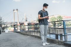 Asian teen in protective mask using smartphone air. Pollution concept royalty free stock image
