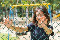 Asian teen smile hand catch welded wire fence Stock Photos