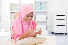 Asian teen texting a message. With her cell phone. Southeast Asian teenager at home. Muslim teenage girl living lifestyle Stock Photo