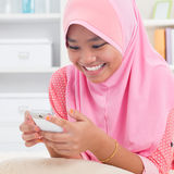 Asian teen texting on the phone. Southeast Asian teenager at home. Muslim teenage girl living lifestyle Stock Images