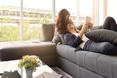 Asian teenage couple make eye contact relaxing on sofa by the royalty free stock image