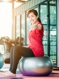Girl exercises. Asian teenage girl exercises with a fitness ball in the fitness center with happiness Stock Photo
