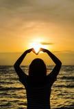 Asian Teenage girl making heart shape in sky Royalty Free Stock Photos