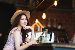 Asian teenage girl smiling in coffee shop with copy space. Cafe culture casual lifestyle, happy traveler woman concept stock image